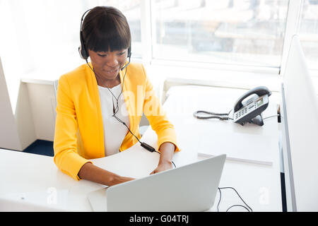 Happy afro american businesswoman in headset using laptop computer in office