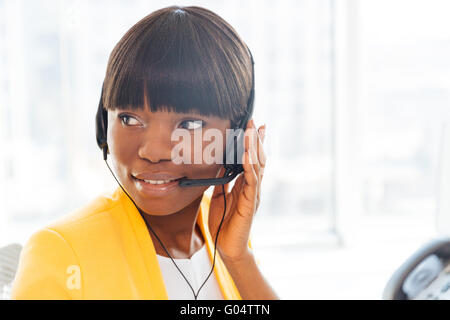 Happy afro american businesswoman working in call center and looking away - Stock Photo