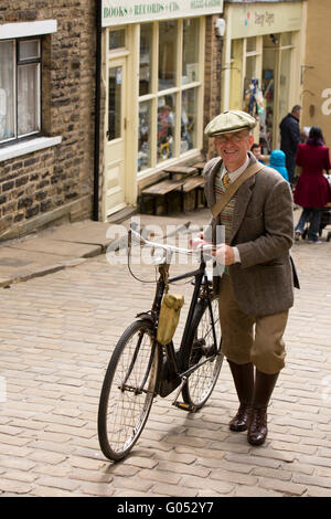 UK, England, Yorkshire, Haworth 40s Weekend, Main Street, Adrian Worral, from St Annes pushing his bike up the hill. - Stock Photo