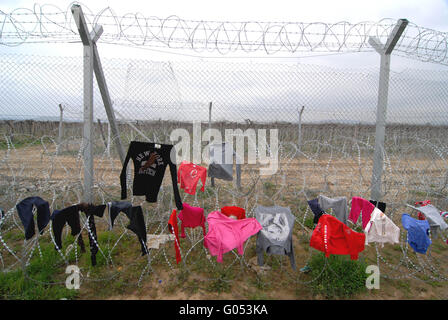 Refugee Camp in Idomeni. Clothes put out to dry on the barbed wire that separates the greek border from the republic - Stock Photo