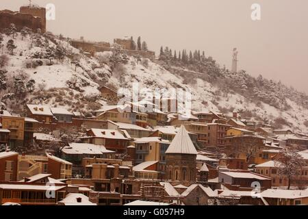 Winter view to covered with snow Tbilisi Old town in misty day - Stock Photo
