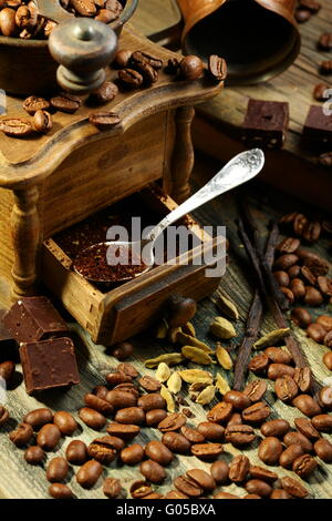 Ground coffee in an old mill, chocolate and cardamom. - Stock Photo