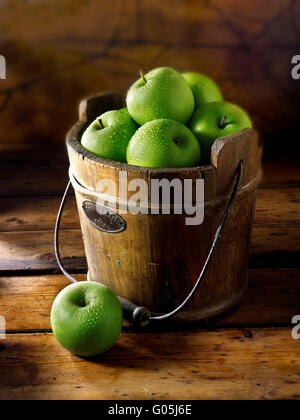 Fresh picked whole Granny Smiths apples in a wooden pale - Stock Photo
