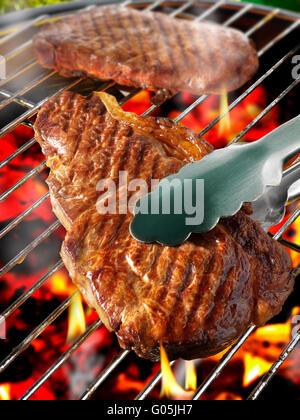 Barbecue steak cooking on a flame bbq grill - Stock Photo