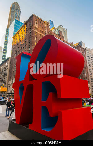 NEW YORK, USA - MAY 06, 2015: Love sculpture by American artist Robert Indiana and tourists passing by in Midtown - Stock Photo