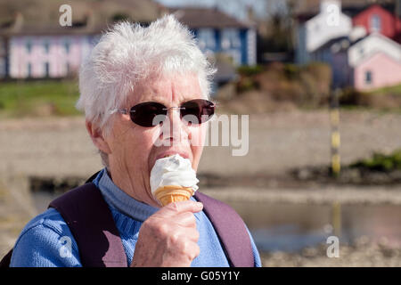 Elderly senior woman older person retiree wearing dark sunglasses and eating an ice cream cone on a sunny summers - Stock Photo
