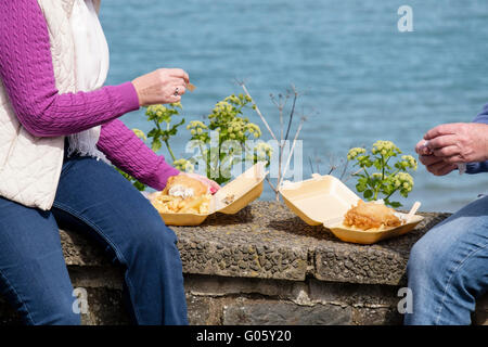 Two people holiday makers sitting on a sea wall eating takeaway fish and chips from polystyrene containers in seaside - Stock Photo