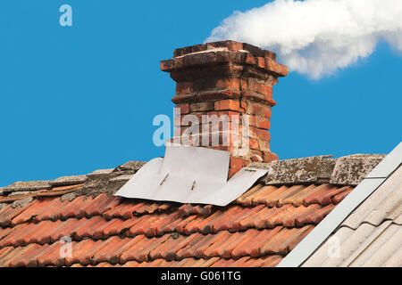 Old pipe from the furnace on the roof out shingles, on blue sky background - Stock Photo