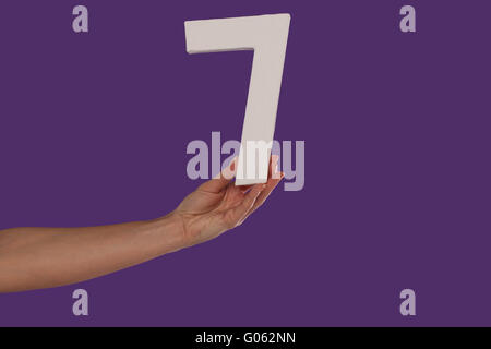 Female hand holding up the number 7 from the left - Stock Photo
