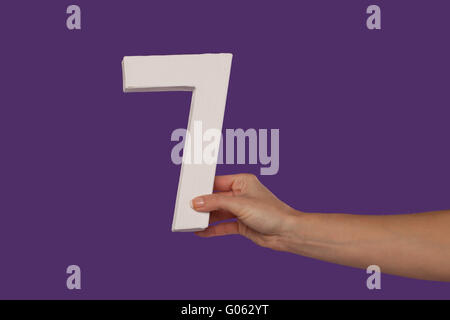 Female hand holding up the number 7 from the right - Stock Photo