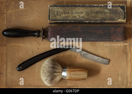 Flat Lay of old Shaving Equipment and german Text for 'Extra fine strop' - Stock Photo