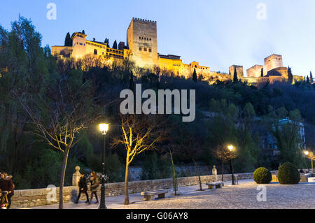 Illuminated Alhambra palace as seen from Paseo de los Tristes street in Albayzin district, Granada, Andalusia, Spain - Stock Photo