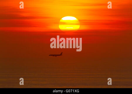 London UK. 29th April 2016. A passenger jet prepares to land over the Mediterranaean sea during a colorful sunset - Stock Photo
