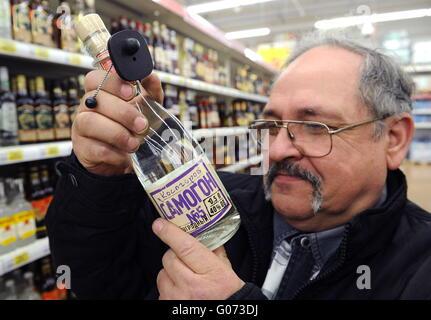 Ryazan, Russia. 7th Apr, 2016. A customer looking at a bottle of Kosogorov Samogon No. 5 in an Auchan hypermarket. - Stock Photo