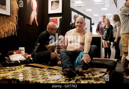 Brighton UK 30th April 2016 - Tattoo artists working at the 9th Annual Brighton Tattoo Convention held in the Brighton - Stock Photo