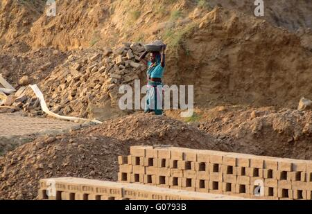 A labor working at a brick factory on the eve of International Labor Day. International Workers' Day, also known - Stock Photo