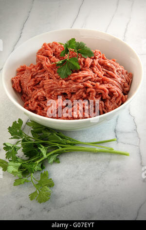 Close up of raw ground beef on marble cutting boar - Stock Photo