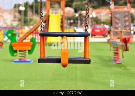 Empty chain swing on modern colorful children playground - Stock Photo