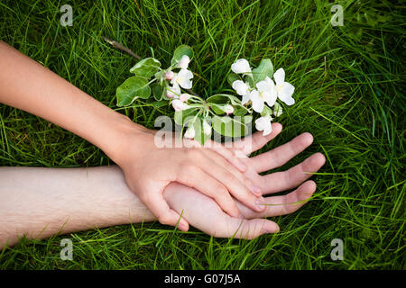hands of lovers on grass with flowers