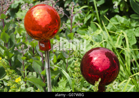 two glassy garden balls on bars at a flower plot - Stock Photo