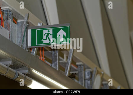 Emergency exit sign in construction site an industrial plant - Stock Photo
