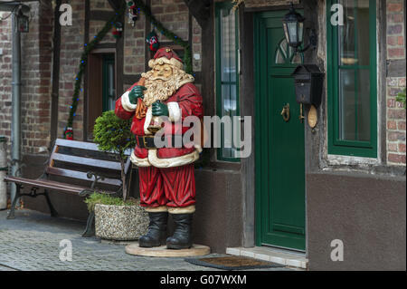 a Santa Claus stands next to the entrance of a res - Stock Photo