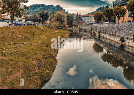River runs thorugh medieval mountain village in Tuscany characterized by houses with walls of stones derived from - Stock Photo