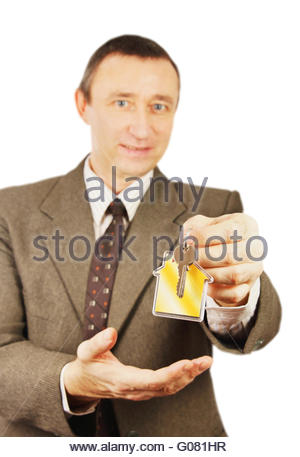 Man offers keys with keychain in the form of a little house - Stock Photo