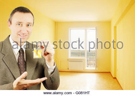Man shows keys with keychain in the form of a little house into a new flat - Stock Photo