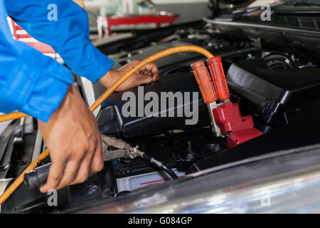 auto mechanic use jumper cables to charge dead car battery