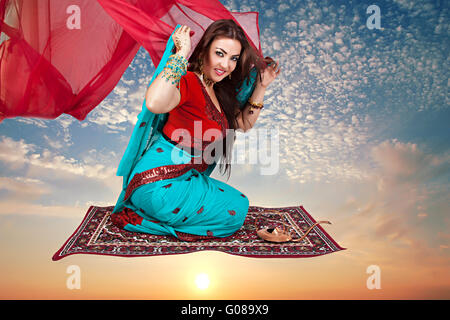 Beautiful young indian woman sitting on a flying c - Stock Photo