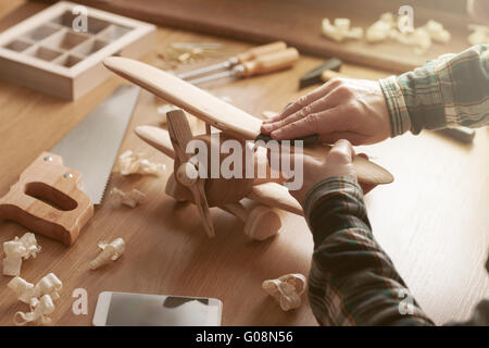 Craftsman smoothing a wooden toy surface with sandpaper, tools and wood shavings all around, hands close up - Stock Photo