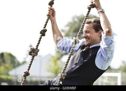 Happy businessman playing, swinging in ropes - Stock Photo