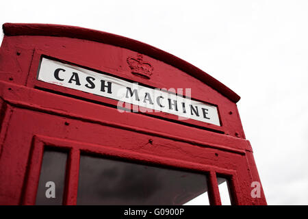 Red telephone booth converted to cash machine - Stock Photo