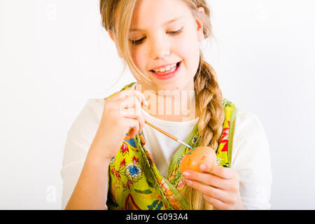 Young girl having fun painting eggs for easter - Stock Photo