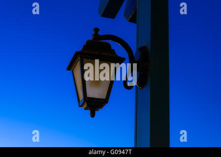 vintage lamp on a pole in the evening after sunset - Stock Photo