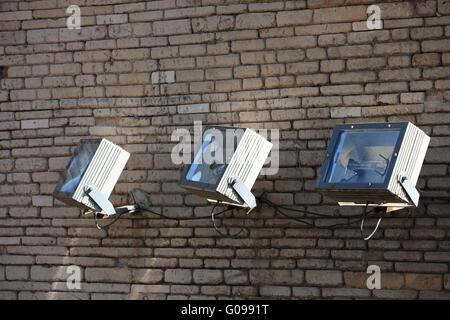 Three spotlights on a brick wall