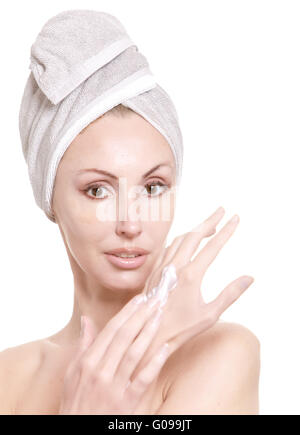 beautiful woman in a towel puts cream on hands - Stock Photo
