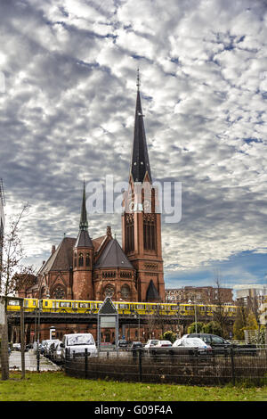 berlin view of a brick church with yellow subway in front on a bridge - Stock Photo