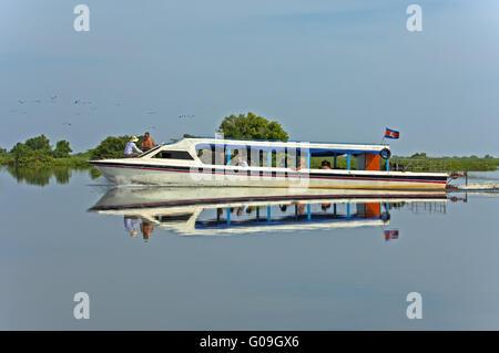 Excursion ship mirrored in the Tonle Sap Lake - Stock Photo