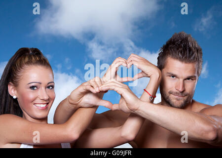 Young couple has joined hands in a heart shape - Stock Photo
