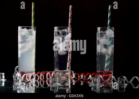 Set from three a collins glass with cocktails and colored straws. Decorated melted ice cubes. - Stock Photo