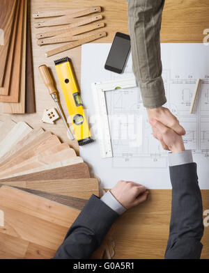 Customer businessman and construction engineer working together on a building project, they are shaking hands, desktop - Stock Photo