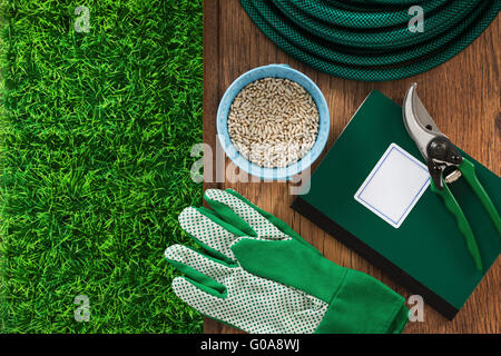 Farming and home gardening tools with green grass and farming manual book guide, top view - Stock Photo