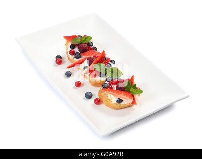 Profiteroles with berries currant  and blueberries - Stock Photo
