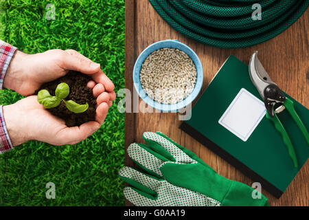 Farmer's hands holding a fresh basil sprout with soil and work tools on background - Stock Photo