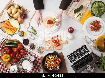 Professional chef's hands cooking pasta on a wooden worktop with vegetables, food ingredients and utensils, top - Stock Photo