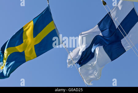 Finland, Sweden, Finnish, Swedish Standards. White, blue and yellow. On top of a ship. Strong wind, sunny. - Stock Photo