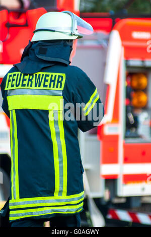 back of a fire fighter with helmet in front of his - Stock Photo