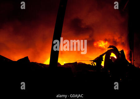 Silhouette of Firemen fighting a raging fire with huge flames - Stock Photo